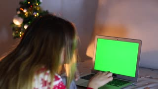 Green Screen Woman's Hand Press Touch on Laptop Keyboard, Lights Bokeh Background From Christmas Tree in Evening.