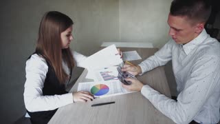 Guy and Girl Sitting at Wooden Table in Work Office. Girl Looks at Graphics and Guy Count Money.