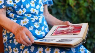 Hands elderly older woman tears watching photo album