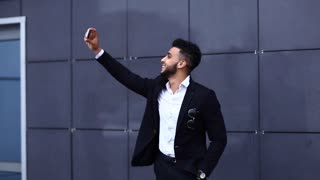 Handsome arabic man takes selfie smart phone in business center