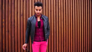 Handsome Young Arabic Guy Posing For Camera and Straightens Jacket or Hair, Smiles and Looks Around on Background of Stairs Outdoors.