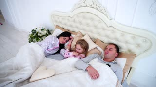 Happy Family Lying in a White Bed and Sleep. Mother, Father and Daughter Together Awake