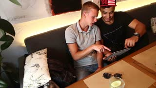 Male friends in cafe talk discuss with technology phone tablet