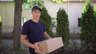 Man Courier Brings Big Order in Hands and Smiling at Camera on Background of Trees and House Outdoors in Daytime.