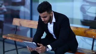 Man in suit arabic use tablet  bored tired near business center