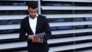 Man in suit arabic with tablet near business shows thumbs down