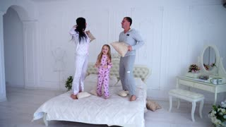 Portrait of Family Jumping on Bed Looking at Camera Together in Pajamas