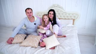 Portrait of Happy Family in Pajamas Smiling and Looking at Camera in Bed Home