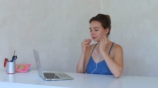 Pretty girl using a laptop with headphones white background