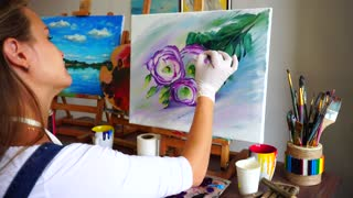 Shooting Artist Girl Behind. Women Draw With Brush on Canvas and Flowers Sitting at Table on Which Art Supplies in Studio.