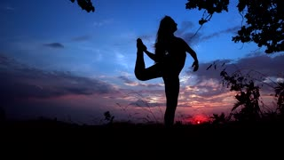 Silhouette Against Bright Color Sunset of One Young Graceful Girl Practicing Yoga Outdoors.