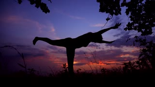 Silhouette Against Pink Purple Sunset of One Young Graceful Girl Practicing Yoga Outdoors.