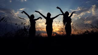 Silhouettes Against Sunset of Three Young Slender Girl Practicing Yoga Breathing Exercise Outdoors.