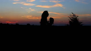 Silhouettes lady against the sunset young beautiful girl with baby dancing