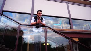 Stately Arabic Male Man Smiling and Standing Stairs and Looks Out From Stairs of Restaurant and Looks Around.