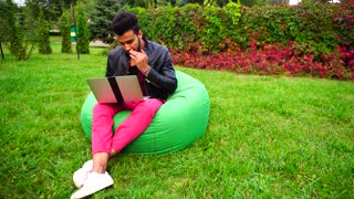 Successful Young Adult Muslim Businessman Sits With Laptop in Chair, Typing on Keyboard, Looks at Screen and Working Online, Rests in Garden Outdoors.