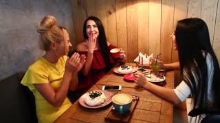 Three beautiful female smile in cafe, talk, tell secrets, eat, d