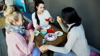 Three Beautiful Female Smile in Cafe, Talk, Tell Secrets, Eat, Drink Coffee.