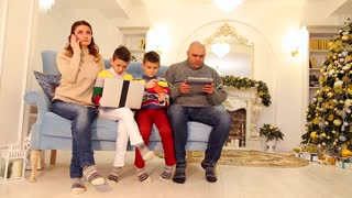 Advanced family, two children and husband and wife are engaged in their own business with gadgets for entertainment, sitting on blue sofa in festive decorated room with tree and fireplace in afternoon
