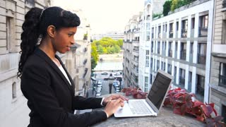 Afro American manager working with laptop on balcony