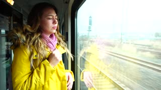 Alluring girl travels in train, makes sad face and weeps, mourns that she leaves beloved city and looks out window after flashing scenery in street in autumn afternoon. European-looking girl with long