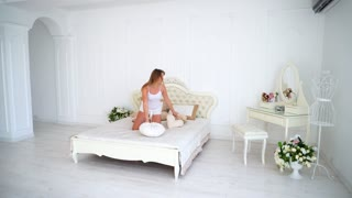 Alluring Young Slim Woman jumping on Bed and With Beautiful Smile Looking at Camera and Posing in Bedroom Girl European Appearance With Long Brown Hair Dressed in White Set of Underwear, T-Shirt and
