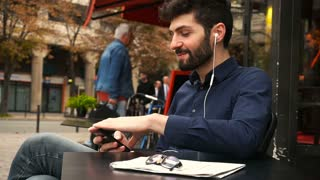 American boy listening to music at cafe with earphones and smartphone in slow motion
