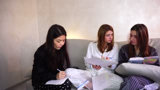 American students do home work, writting English text for classes. European-looking girl with medium-length fair-haired hair dressed in light pajamas in polka dots, second girl with fair-haired hair