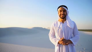 Arab male sales representative looks at camera and tells information, takes money in hands, standing in middle of wide desert on summer evening outdoors