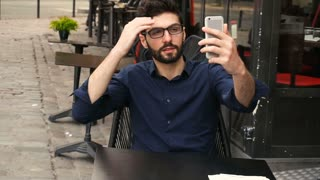 Arabic man making selfie with smartphone at cafe table