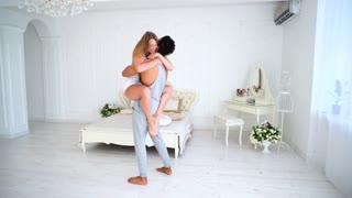 Arabic Young and Muscular Guy and Beautiful Girl Like Soul Mate. Women Leaping Into Arms to Embrace Beloved and Tenderly Whispers Sweet Words in Spacious Bright and Cozy Bedroom Near Bed Big and