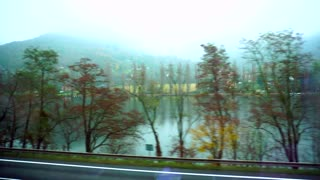 Autumn landscape from train window in motion on cloudy autumn day. Transport rushes at speed, passing through long river and high mountains, tops of which are in fog.  Concept of view of nature fro