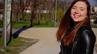 Beautiful female person passing with laptop and looking at camera. Concept of modern gadget and good spring weather. Young woman wears black leather jacket and has long brown hair.