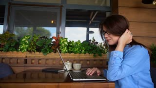 Beautiful girl browsing by laptop at cafe