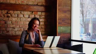 Beautiful girl sitting at cafe with brick wall background and chatting with boyfriend by laptop. Concept of hotspot for customers at restaurants. Pretty female person has pigtail hairstyle.