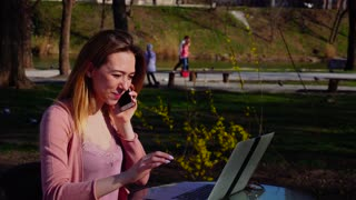 Beautiful girl talking by smartphone and working with laptop in park. Concept of communication with close people, advantageous tariff plan. Young woman has good mood.