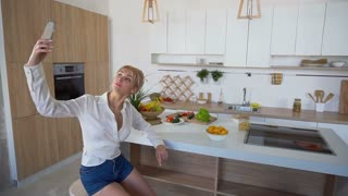 Beautiful woman doing selfie on phone on background of kitchen table with vegetables and fruits sitting on chair in modern kitchen