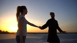 Beloved Arabian guy and European girl hold hands and walk along sand dunes of desert on summer evening in open air