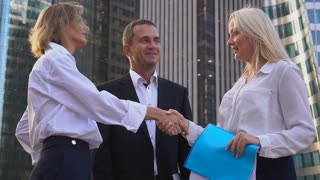 Biz team members shaking hands in La Defense Paris, slow motion