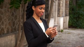 Black female person chatting on smartphone outside