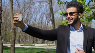Blogger making video on new phone and showing thumbing up and peace finger sign in slow motion