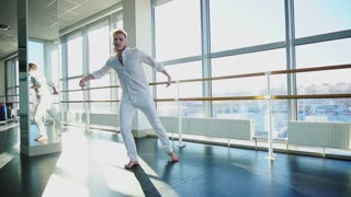 Blonde guy doing vigorous movements in white suit