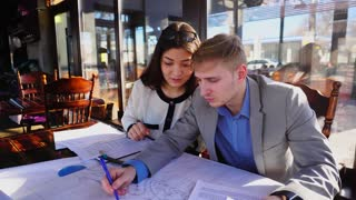 Boy helping girlfriend with architect home task drafting at cafe table