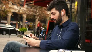 Boy talking with girlfriend by smartphone video call and earphones at cafe