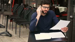 Businessman arguing by smartphone and reading papers at cafe table