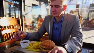 Businessman dressed in grey jacket with smart watch enjoying eating fast food