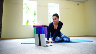 Businesswoman studies basic yoga exercises on online course