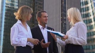 Businesswomen speaking with male boss outside