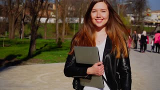 Charming European woman walking with laptop and closed eyes near park. Concept of enjoying with good spring weather. Young female person wears leather jacket and has cute smile.