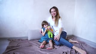 Charming girl and caring mom smiling and posing at camera, little girl playing with doll and keychain, women together happily waving their hands in camera lens, sitting on floor in bright room. Woman